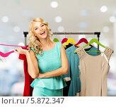 Купить «Веселая блондинка выбирает одежду на стойке в магазине», фото № 5872347, снято 29 апреля 2014 г. (c) Andrejs Pidjass / Фотобанк Лори