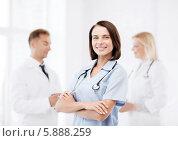 Купить «Молодая женщина-врач стоит, скрестив руки на фоне разговаривающих между собой коллег», фото № 5888259, снято 6 июля 2013 г. (c) Syda Productions / Фотобанк Лори