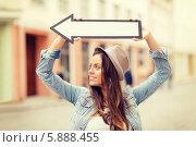 Купить «Девушка с длинными волосами и в шляпе держит над головой стрелку, указывая направление в городе», фото № 5888455, снято 29 июня 2013 г. (c) Syda Productions / Фотобанк Лори