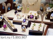 Купить «Кольца с драгоценными камнями на прилавке магазина», фото № 5893907, снято 15 апреля 2014 г. (c) Яков Филимонов / Фотобанк Лори