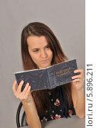 Купить «Девушка с недовольством смотрит в зачетную книжку», фото № 5896211, снято 30 января 2013 г. (c) Малышев Андрей / Фотобанк Лори