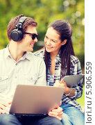 Купить «Молодой человек с ноутбуком в наушниках и девушка с планшетным компьютером разговаривают в парке», фото № 5906559, снято 15 сентября 2013 г. (c) Syda Productions / Фотобанк Лори
