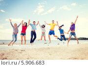 Купить «Группа молодых людей одновременно прыгают на песчаном пляже», фото № 5906683, снято 31 августа 2013 г. (c) Syda Productions / Фотобанк Лори