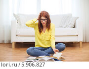 Купить «Серьезная девушка сидит на полу дома, скрестив ноги, и читает учебники», фото № 5906827, снято 19 марта 2014 г. (c) Syda Productions / Фотобанк Лори
