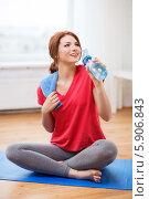 Купить «Девушка в красной футболке пьет воду из пластиковой бутылки, сидя на коврике для фитнеса», фото № 5906843, снято 19 марта 2014 г. (c) Syda Productions / Фотобанк Лори