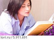 Девушка лежит на кровати и читает книгу. Стоковое фото, фотограф Евгений Леонов / Фотобанк Лори