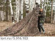 Купить «Охотник закрепляет маскировочную сеть», фото № 5916103, снято 4 мая 2014 г. (c) Павел Родимов / Фотобанк Лори