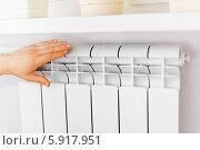 Купить «Рука прикасается к белому радиатору. Проверка отопления», фото № 5917951, снято 18 мая 2014 г. (c) Vitas / Фотобанк Лори