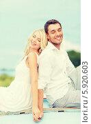 Купить «Счастливые молодые мужчина и женщина сидят на улице спиной друг к другу», фото № 5920603, снято 14 июля 2013 г. (c) Syda Productions / Фотобанк Лори