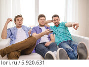 Купить «Трое друзей сидят дома на диване с пультом от телевизора», фото № 5920631, снято 22 марта 2014 г. (c) Syda Productions / Фотобанк Лори
