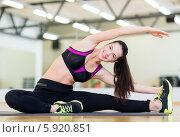 Купить «Девушка в спортивном зале выполняет наклоны сидя на специальном коврике», фото № 5920851, снято 28 сентября 2013 г. (c) Syda Productions / Фотобанк Лори