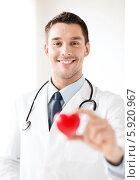 Купить «Молодой врач с дружелюбной улыбкой держит в руке красное сердце», фото № 5920967, снято 18 мая 2013 г. (c) Syda Productions / Фотобанк Лори