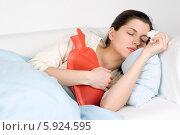 Купить «Девушка с симптомами ОРВИ лежит в постели с грелкой и носовым платком», фото № 5924595, снято 26 марта 2019 г. (c) BE&W Photo / Фотобанк Лори