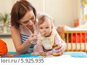 Купить «Женщина кормит маленькую дочку детским пюре», фото № 5925935, снято 22 мая 2018 г. (c) BE&W Photo / Фотобанк Лори