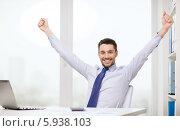 Купить «Радостный бизнесмен поднял обе руки вверх, сидя за столом в офисе», фото № 5938103, снято 15 марта 2014 г. (c) Syda Productions / Фотобанк Лори