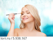 Привлекательная блондинка с кисточкой для макияжа наносит тени. Стоковое фото, фотограф Syda Productions / Фотобанк Лори