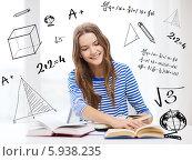 Купить «Подготовка к экзаменам. Девушка сидит за столом с учебниками на фоне стены с чертежами и формулами», фото № 5938235, снято 26 февраля 2014 г. (c) Syda Productions / Фотобанк Лори