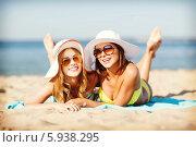 Купить «Две подруги в широкополых летних шляпах загорают на песчаном пляже», фото № 5938295, снято 11 июля 2013 г. (c) Syda Productions / Фотобанк Лори