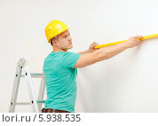 Купить «Рабочий в желтой строительной каске использует уровень для выравнивания стен», фото № 5938535, снято 16 февраля 2014 г. (c) Syda Productions / Фотобанк Лори