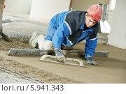Купить «Строительный рабочий разравнивает раствор на полу», фото № 5941343, снято 12 мая 2014 г. (c) Дмитрий Калиновский / Фотобанк Лори