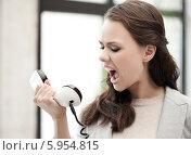 Купить «Рассерженная девушка громко кричит в телефонную трубку», фото № 5954815, снято 16 июля 2011 г. (c) Syda Productions / Фотобанк Лори