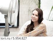 Купить «Девушка улыбается, сидя дома рядом с вентилятором», фото № 5954827, снято 16 июля 2011 г. (c) Syda Productions / Фотобанк Лори