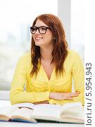 Купить «Студентка в аудитории внимательно слушает, сидя за столом с учебниками», фото № 5954943, снято 19 марта 2014 г. (c) Syda Productions / Фотобанк Лори