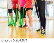 Купить «Ноги людей, занимающихся в спортивном зале с фитнес-резинкой», фото № 5954971, снято 28 сентября 2013 г. (c) Syda Productions / Фотобанк Лори