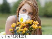 Купить «Красивая рыжая девушка в защитной маске с букетом цветов. Аллергия», фото № 5961239, снято 19 марта 2019 г. (c) BE&W Photo / Фотобанк Лори
