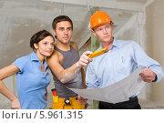 Купить «Молодая пара обсуждает ремонт в квартире с прорабом», фото № 5961315, снято 21 мая 2019 г. (c) BE&W Photo / Фотобанк Лори