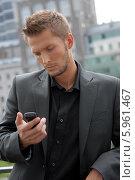Элегантный мужчина в костюме смотрит на мобильный телефон. Стоковое фото, агентство BE&W Photo / Фотобанк Лори