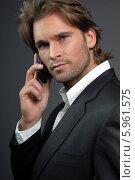 Привлекательный молодой мужчина в темном костюме разговаривает по телефону. Стоковое фото, агентство BE&W Photo / Фотобанк Лори