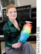 Купить «Очаровательная блондинка в зеленой блузке с метелкой для вытирания пыли сидит у рояля», фото № 5971435, снято 17 октября 2018 г. (c) BE&W Photo / Фотобанк Лори
