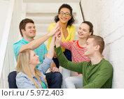 Купить «Друзья сидя на лестнице сложили руки ладонями вместе», фото № 5972403, снято 29 марта 2014 г. (c) Syda Productions / Фотобанк Лори