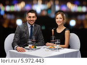 Праздничный вечер в ресторане. Молодая пара сидит за столиком. Стоковое фото, фотограф Syda Productions / Фотобанк Лори