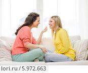 Купить «Девушка что-то рассказывает своей подруге, сидящей напротив нее на диване», фото № 5972663, снято 12 апреля 2014 г. (c) Syda Productions / Фотобанк Лори