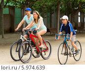 Купить «Веселая семья из трех человек катается на велосипедах», фото № 5974639, снято 17 мая 2014 г. (c) Яков Филимонов / Фотобанк Лори