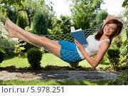 Купить «Прекрасная молодая девушка отдыхает в гамаке в саду и читает книгу», фото № 5978251, снято 15 августа 2018 г. (c) BE&W Photo / Фотобанк Лори