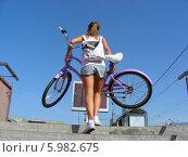 Молодая девушка несет велосипед по переходному переходу, не оборудованному пандусом (2014 год). Редакционное фото, фотограф lana1501 / Фотобанк Лори