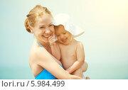 Купить «Счастливая мама с дочкой на руках на морском пляже», фото № 5984499, снято 28 мая 2014 г. (c) Евгений Атаманенко / Фотобанк Лори