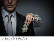 Купить «Бизнесмен с долларами в кармане пиджака», фото № 5986739, снято 19 декабря 2013 г. (c) Raev Denis / Фотобанк Лори