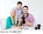 Купить «Молодые сотрудники в офисе с фотоаппаратом», фото № 5988891, снято 17 мая 2014 г. (c) Syda Productions / Фотобанк Лори