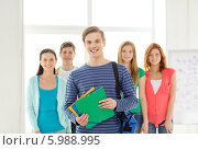 Купить «Улыбающийся молодой человек стоит впереди своих друзей с папками в руках и сумкой для ноутбука», фото № 5988995, снято 4 мая 2014 г. (c) Syda Productions / Фотобанк Лори