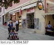 Пожилая женщина везет двух маленьких детей в коляске по улице европейского города (2008 год). Редакционное фото, фотограф Татьяна Чечина / Фотобанк Лори