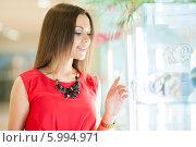 Купить «Красивая девушка с длинными волосами в красном платье делает покупки», фото № 5994971, снято 10 июня 2014 г. (c) Вера Франц / Фотобанк Лори