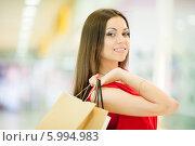 Купить «Красивая девушка с длинными волосами в красном платье делает покупки, держит пакеты», фото № 5994983, снято 10 июня 2014 г. (c) Вера Франц / Фотобанк Лори