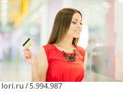 Купить «Красивая девушка с длинными волосами в красном платье делает покупки, держит кредитную карту», фото № 5994987, снято 10 июня 2014 г. (c) Вера Франц / Фотобанк Лори