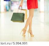 Купить «Стройная девушка в красном платье идет по магазину с пакетами покупок», фото № 5994991, снято 10 июня 2014 г. (c) Вера Франц / Фотобанк Лори