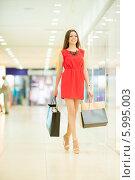 Купить «Красивая девушка с длинными волосами в красном платье делает покупки, идет по магазину», фото № 5995003, снято 10 июня 2014 г. (c) Вера Франц / Фотобанк Лори