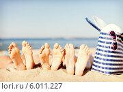 Купить «Ноги трех людей, загорающих на пляже», фото № 6011227, снято 11 июля 2013 г. (c) Syda Productions / Фотобанк Лори
